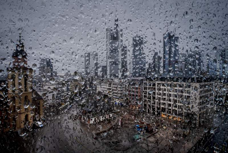 The buildings of the banking district are photographed through raindrops on a window in Frankfurt, Germany, Tuesday, March 10, 2020. (AP Photo/Michael Probst)