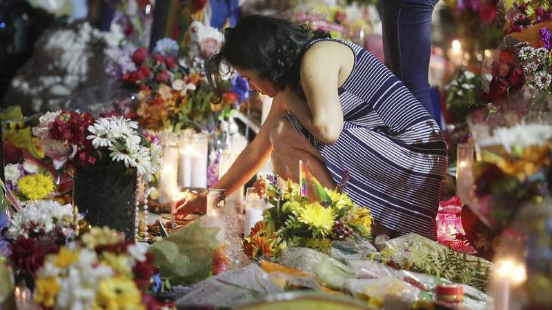Mourners light candles at the Pulse nightclub in Orlando, Fla., Monday, June 12, 2017. A gunman opened fire at the nightclub one year ago in the worst mass shooting in modern U.S. history, killing 49 people. (Stephen M. Dowell/Orlando Sentinel via AP, Pool)