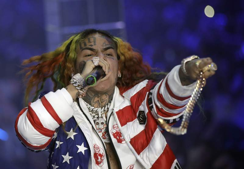 FILE- In this Sept. 21, 2018, file photo rapper Daniel Hernandez, known as Tekashi 6ix9ine, performs during the Philipp Plein women's 2019 Spring-Summer collection, unveiled during the Fashion Week in Milan, Italy.  Bodyguards for troubled rapper Tekashi 6ix9ine turned New York City into the Wild West last summer, piling into SUVs and chasing a man for 20 blocks with lights flashing after he attempted to record cellphone video of the recording star, prosecutors said Monday, July 19, 2021.  (AP Photo/Luca Bruno, File)