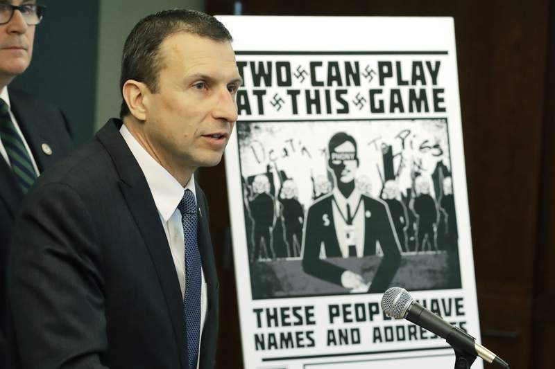 FILE - In this Feb. 26, 2020, file photo, Raymond Duda, FBI Special Agent in Charge in Seattle, speaks as he stands next to a poster that was mailed earlier in the year to the home of Chris Ingalls, an investigative reporter with KING-TV during a news conference in Seattle. A federal judge declined to impose prison time Wednesday, March 31, 2021, on a former member of a neo-Nazi ring that made threats against journalists, finding that the 21-year-old, who concealed his transgender identity from his co-conspirators, had already suffered enough in his young life. (AP Photo/Ted S. Warren, File)