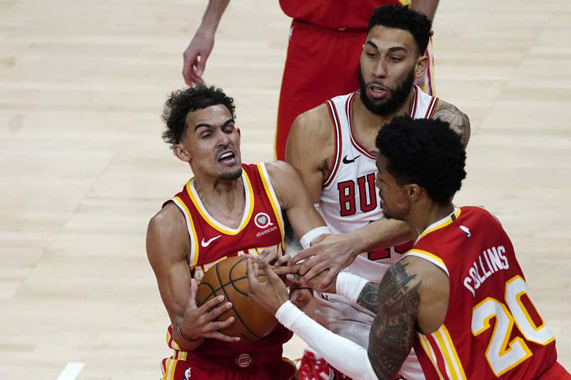 Atlanta Hawks guard Trae Young, left, and John Collins (20) battle Chicago Bulls guard Denzel Valentine (45) in the second half of an NBA basketball game Saturday, May 1, 2021, in Atlanta. (AP Photo/John Bazemore)