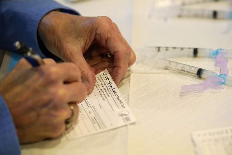 FILE - In this Tuesday, Dec. 29, 2020 file photo, a county health department worker fills out a vaccination record card before administering the Moderna COVID-19 vaccine to emergency medical workers and healthcare personnel at the Chester County Government Services Center in West Chester, Pa. The first coronavirus vaccines in the U.S. require two shots taken weeks apart, and you'll be given a record card so you know when to go back for the second dose. (AP Photo/Matt Slocum)