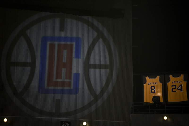 The retired jerseys of late Los Angeles Lakers' Kobe Bryant hangs above the arena next to a projected logo of the Los Angeles Clippers prior to an NBA basketball game against the Sacramento Kings in Los Angeles, Thursday, Jan. 30, 2020. (AP Photo/Kelvin Kuo)