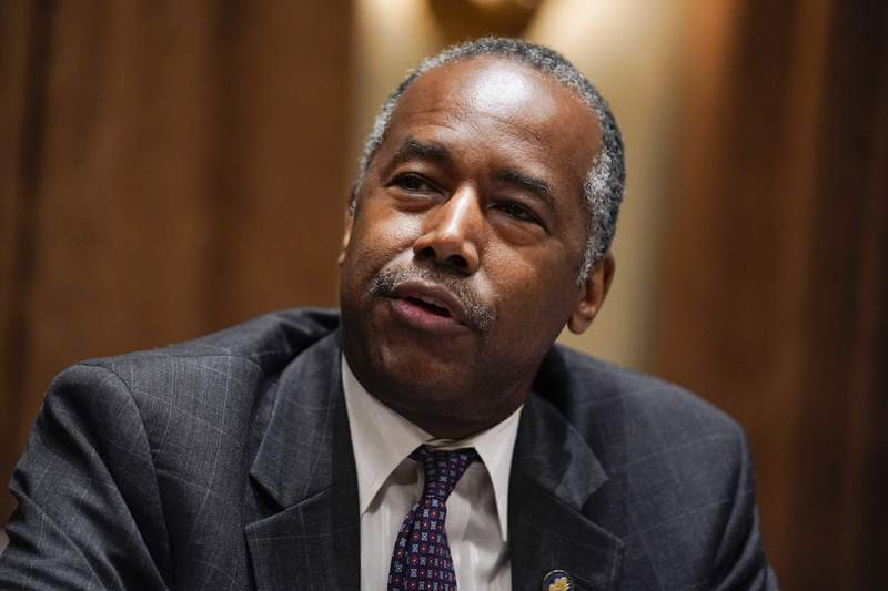 FILE - In this June 15, 2020, file photo Housing and Urban Development Secretary Ben Carson speaks during a roundtable with President Donald Trump about America's seniors, in the Cabinet Room of the White House in Washington. The Trump administration said Thursday, July 23, that it is revoking an Obama-era housing regulation designed to eliminate racial disparities in the suburbs. In a statement, Carson said the regulation known as Affirmatively Furthering Fair Housing, or the AFFH rule, was unworkable and ultimately a waste of time for localities to  comply with.  (AP Photo/Evan Vucci, File)