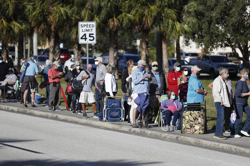 FORT MYERS, FL - DECEMBER 30: Seniors and first responders wait in line to receive a COVID-19 vaccine at the Lakes Regional Library on December 30, 2020 in Fort Myers, Florida. There were 800 doses of vaccine available at the site. (Photo by Octavio Jones/Getty Images)