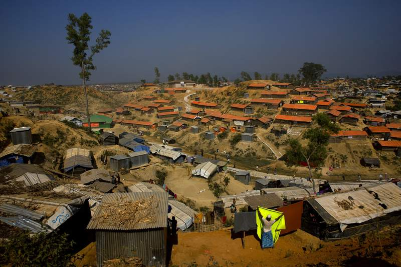 FILE - In this Jan. 23, 2018 file photo, a Rohingya refugee hangs a blanket out to dry at Balukhali refugee camp, about 50 kilometers (32 miles) from Cox's Bazar, Bangladesh. An island in Bangladesh that was submerged during the monsoon season is ready to house 100,000 Rohingya refugees, but no date has been announced to begin relocating people from crowded and squalid camps on the country's border with Myanmar, officials said Thursday. (AP Photo/Manish Swarup, File)