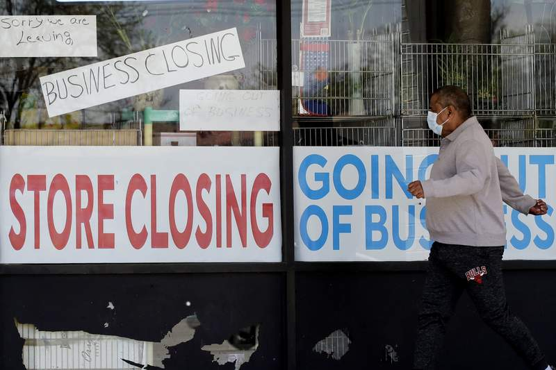 FILE - In this May 21, 2020 file photo, a man looks at signs of a closed store due to COVID-19 in Niles, Ill.   U.S. businesses shed 2.76 million jobs in May, as the economic damage from the historically unrivaled coronavirus outbreak stretched into a third month. The payroll company ADP reported Wednesday that businesses have let go of a combined 22.6 million jobs since March.AP Photo/Nam Y. Huh, File)