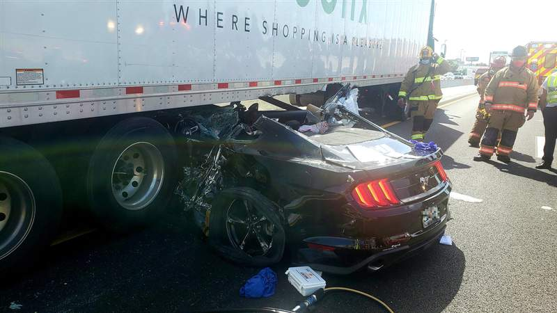A Ford Mustang is crushed after getting stuck underneath a Publix delivery truck in a crash that shut down westbound State Road 528 in Orange County. (Image: Orange County Fire Rescue)