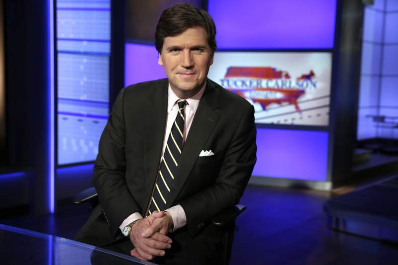 """FILE - In this March 2, 20217, file photo, Tucker Carlson, host of """"Tucker Carlson Tonight,"""" poses for photos in a Fox News Channel studio in New York. A steady criticism of COVID vaccine mandates by figures on Fox News has drawn attention to its own company's stringent rules on the topic  even from President Joe Biden. Carlson devoted nearly the first 20 minutes of his show on Sept. 15, 2020, to Biden's COVID efforts, saying the rules require people to submit to being bullied. (AP Photo/Richard Drew, File)"""