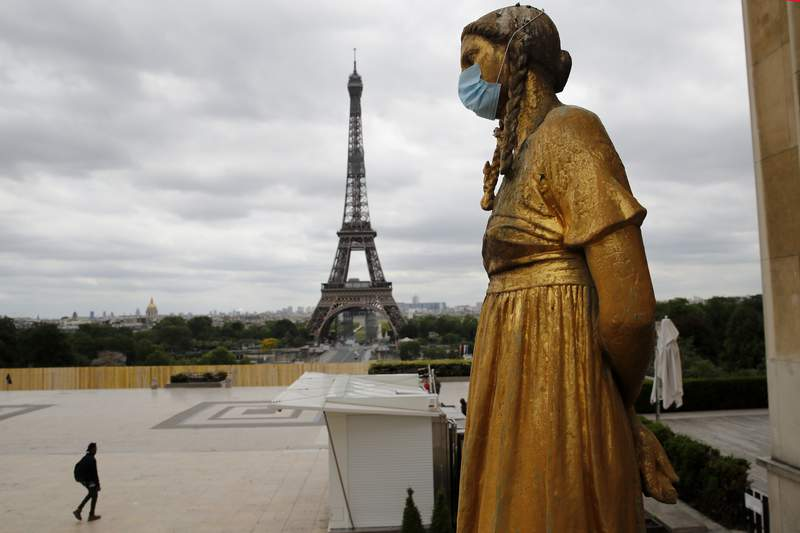 FILE- In this file photo dated Monday, May 4, 2020, a statue wears a mask along Trocadero square close to the Eiffel Tower in Paris.  In a study published Tuesday May 5, 2020, in the International Journal of Microbial Agents, doctors at a hospital north of Paris reviewed retrospective samples of 14 patients treated for atypical pneumonia, and say they may have identified a possible case of the new coronavirus dating back to December 2019. (AP Photo/Christophe Ena, FILE)