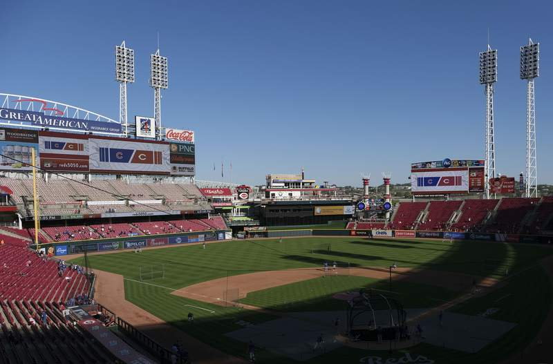 Fans watch players warm up for a baseball game between the Chicago Cubs and the Cincinnati Reds at Great American Ball Park in Cincinnati on Friday, April 30, 2021. (AP Photo/Jeff Dean)