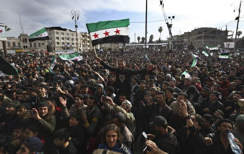 In this March 15, 2021, photo, thousands of anti-Syrian government protesters shout slogans and wave revolutionary flags, to mark 10 years since the start of a popular uprising against President Bashar Assad's rule, that later turned into an insurgency and civil war, in Idlib, the last major opposition-held area of the country, in northwest Syria. The Biden administration is mulling over Americas role in Syrias ongoing conflict as the U.S. tries to break away from Middle East wars. But Vladimir Putins top diplomat already has been busy on the ground, trying to win support for a Syria approach that could establish Russia as a broker of security and power in the region. (AP Photo/Ghaith Alsayed)