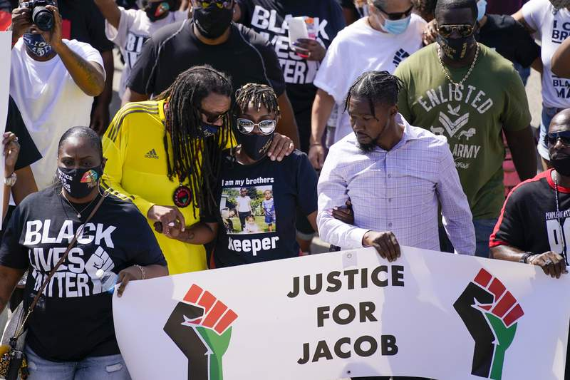 FILE - In this Aug. 29, 2020, file photo, Jacob Blake's sister Letetra Widman, center, and uncle Justin Blake, left, march at a rally for Jacob Blake Saturday, Aug. 29, 2020, in Kenosha, Wis. Authorities have been reluctant to release even the most basic information about the incident or details about the white officer who shot Blake seven times in the back. (AP Photo/Morry Gash, File)