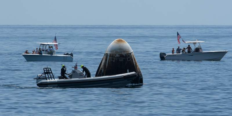 Support teams and curious recreational boaters arrive at the SpaceX Crew Dragon Endeavour spacecraft shortly after it landed with NASA astronauts Robert Behnken and Douglas Hurley onboard in the Gulf of Mexico off the coast of Pensacola, Florida, Sunday, Aug. 2, 2020. The Demo-2 test flight for NASA's Commercial Crew Program was the first to deliver astronauts to the International Space Station and return them safely to Earth onboard a commercially built and operated spacecraft. Behnken and Hurley returned after spending 64 days in space. Photo Credit: (NASA/Bill Ingalls)