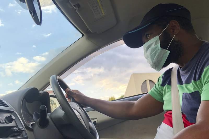 In this April 15, 2020, photo, AP photojournalist Tsvangirayi Mukwazhi approaches a police roadblock in his car in Harare, Zimbabwe. (AP Photo/Tsvangirayi Mukwazhi)