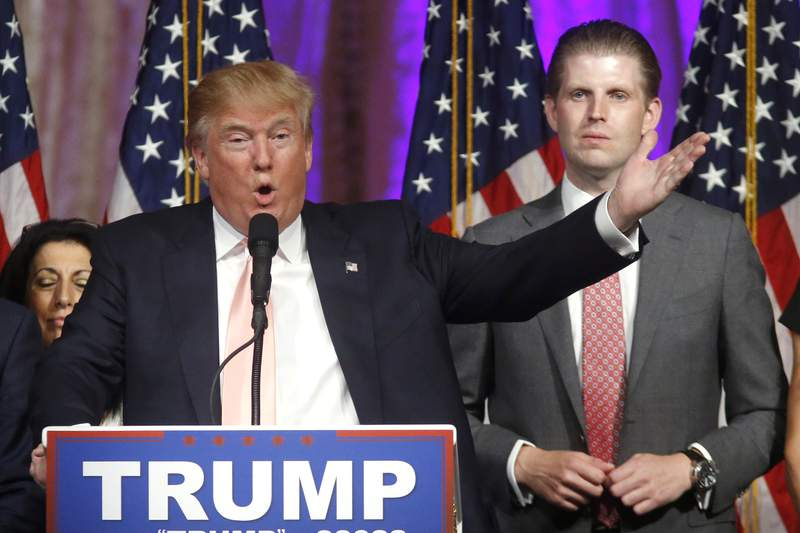 FILE - In this Tuesday, March 15, 2016, file photo, Republican presidential candidate Donald Trump speaks to supporters at his primary election night event at his Mar-a-Lago Club in Palm Beach, Fla. At right is his son Eric Trump. Hits to President Donald Trumps business empire since the deadly riots at the U.S. Capitol are part of a liberal cancel culture, his son Eric told The Associated Press on Tuesday, Jan. 12, 2021, saying his father will leave the presidency with a powerful brand backed by millions of voters who will follow him to the ends of the Earth. (AP Photo/Gerald Herbert, File)