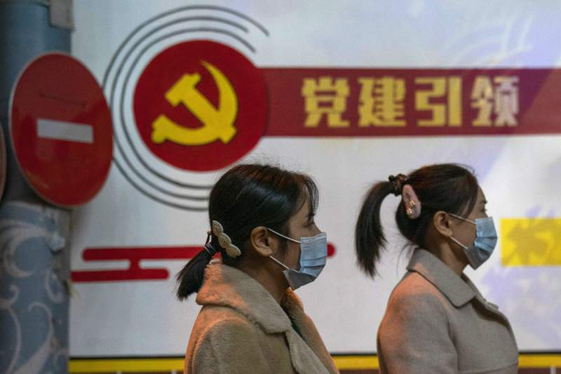 """Residents wearing masks pass by the Communist party logo and the slogan """"Party building leadership"""" in Beijing on Thursday, Oct. 29, 2020. China will promote """"technological self-reliance"""" under the ruling Communist Party's latest five-year plan but will open further to trade, officials said Friday. (AP Photo/Ng Han Guan)"""