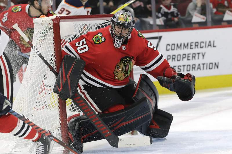 FILE - In this March 5, 2020, file photo, then-Chicago Blackhawks goalie Corey Crawford watches the puck during the second period of an NHL hockey game against Edmonton in Chicago. Lots of new faces at the New Jersey Devils training camp, with the most-well known being 36-year-old goaltender Corey Crawford, who was signed as a free agent along with defenseman Dmitry Kulikov. (AP Photo/Nam Y. Huh, File)