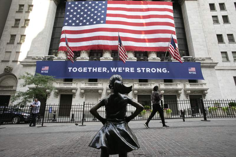 FILE - In this July 9, 2020 file photo, the Fearless Girl statue stands in front of the New York Stock Exchange in New York. Stocks are off to a mixed start, Thursday, Dec. 31,  on Wall Street on the last day of 2020, a year that saw a breathtaking nosedive in markets in the spring as the coronavirus took hold followed by steady gains in the months that followed as hopes built for an eventual return to something like normal.  (AP Photo/Mark Lennihan, File)