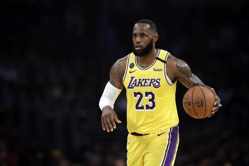 FILE - In this March 10, 2020, file photo, Los Angeles Lakers' LeBron James (23) dribbles during the first half of an NBA basketball game against the Brooklyn Nets in Los Angeles. If James gets his way, NBA arenas and other sports venues around the country will be mega polling sites for the November general election. (AP Photo/Marcio Jose Sanchez, File)