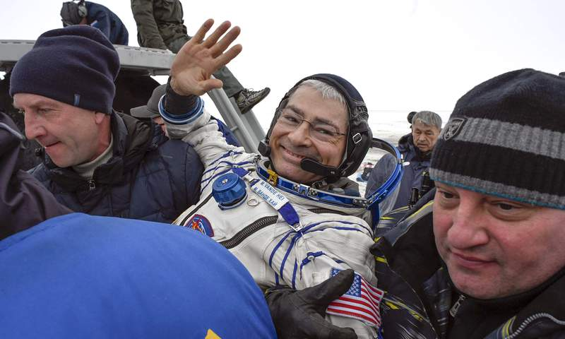 FILE - In this Feb. 28, 2018 file photo, ground personnel carry NASA astronaut Mark Vande Hei after the landing of the Soyuz MS-06 space capsule in a remote area south-east of the Kazakh town of Zhezkazgan, Kazakhstan. Vande Hei learned last week that hell launch April 9, 2021, on a Russian rocket to the International Space Station.Vande Hei said Monday, March 15 he may have to give up his return Soyuz seat in the fall to a Russian movie-making tourist. If that happens, he'll have to wait for the next Soyuz ride home in spring 2022.  (Alexander Nemenov/Pool Photo via AP, File)