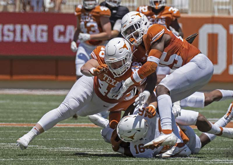 FILE - In this April 24, 2021, file photo, Texas defenders Jake Ehlinger, left, and B.J. Foster, right, tackle Kayvontay Dixon (16) during the first half of the Orange and White spring scrimmage college football game in Austin, Texas. Ehlinger, the younger brother of former Longhorns quarterback Sam Ehlinger, was found dead near campus Thursday, May 6, Austin police said. Officers found the 20-year-old Ehlinger after responding to a call at 12:18 p.m. Police did not detail how they found him but said the death is not considered suspicious. No cause of death was immediately released. (AP Photo/Michael Thomas, File)