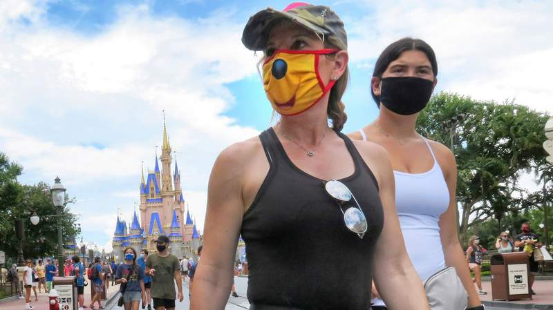 Guests wear masks as required to attend the official reopening day of the Magic Kingdom at Walt Disney World in Lake Buena Vista, Fla., on July 11, 2020.