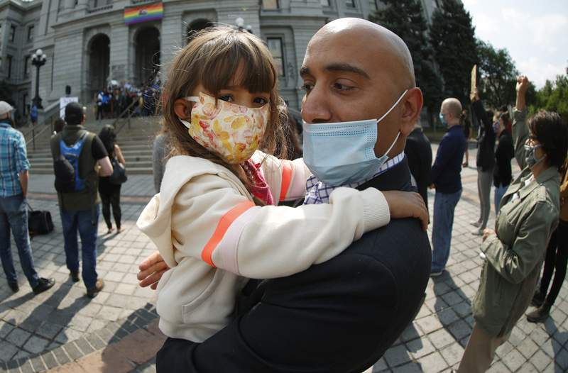 Three-year-old Amira Salahuddin, left, and her father, Faisal, both of Denver, wear face masks while attending a news conference on the west steps of the State Capitol, Friday, June 19, 2020, in downtown Denver. (AP Photo/David Zalubowski)