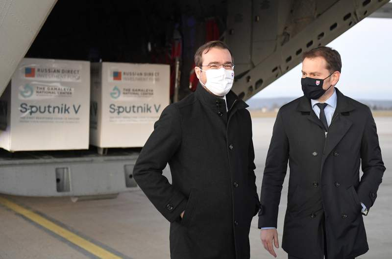 FILE - In this Monday March 1, 2021 file photo, Slovak Prime Minister Igor Matovic, right, and Health Minister Marek Krajci at Kosice Airport, Slovakia, as Russia's Sputnik V coronavirus vaccine arrives. Two parties in Slovakias ruling coalition called on the conservative prime minister to resign to open the way for a reconstruction of the government amid a political crisis triggered by a secret deal to buy Russia's coronavirus vaccine. (Frantisek Ivan/TASR via AP, File)