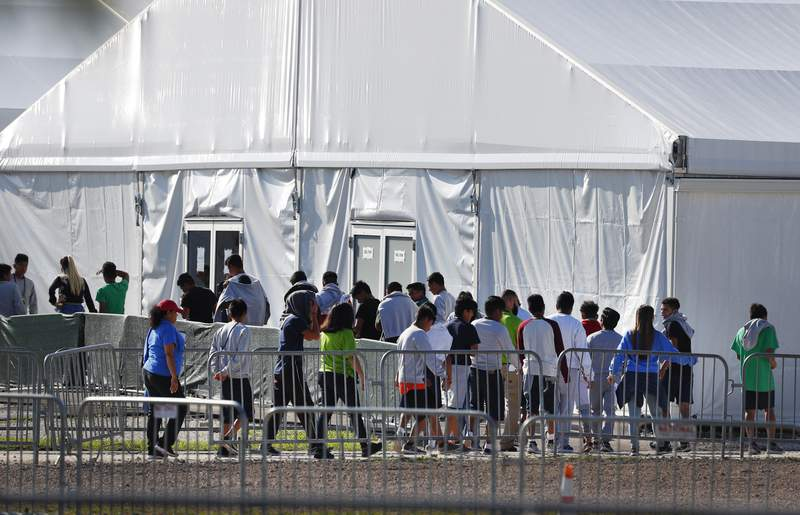 FILE- In this Feb. 19, 2019, file photo, children line up to enter a tent at the Homestead Temporary Shelter for Unaccompanied Children in Homestead, Fla.  Despite efforts by the Trump administration to improve communication to track children who are separated from their families at the border, the process is still vulnerable to error and information sharing between agencies is inconsistent, raising questions on the accuracy of current data, a watchdog reported Thursday.  (AP Photo/Wilfredo Lee, File)