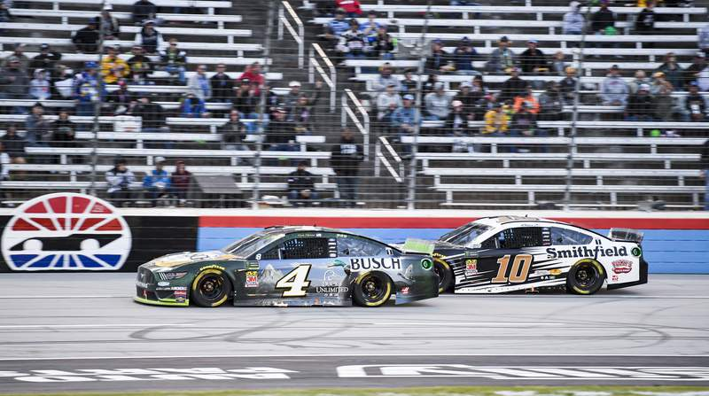 FILE - In this Nov. 3, 2019, file photo, Kevin Harvick (4) and Aric Almirola (10) battle for position during a NASCAR Cup Series auto race at Texas Motor Speedway, in Fort Worth, Texas. The massive grandstands at Texas Motor Speedway stretch about 2/3 of a mile long, and were empty for the last race there. There could still be some feeling of emptiness Sunday, preferable for social distancing, even when the NASCAR Cup Series race becomes the first major sporting event in Texas in more than four months to allow spectators. It will be one of the largest gatherings of any kind in the state since the start of the coronavirus pandemic. (AP Photo/Larry Papke, File)