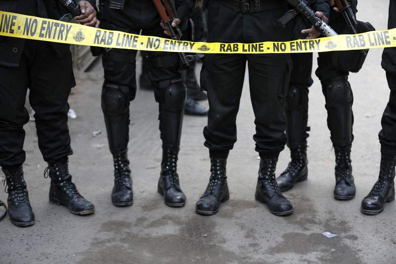 FILE -In this Jan 12, 2018 file photo, members of Rapid Action Battalion guard an area during an operation in Dhaka, Bangladesh. A global human rights group urged the United Nations on Monday to lead an independent investigation into the alleged disappearances of government critics and others at the hands of security forces in Bangladesh, an allegation the country's government has long denied. (AP Photo, File)