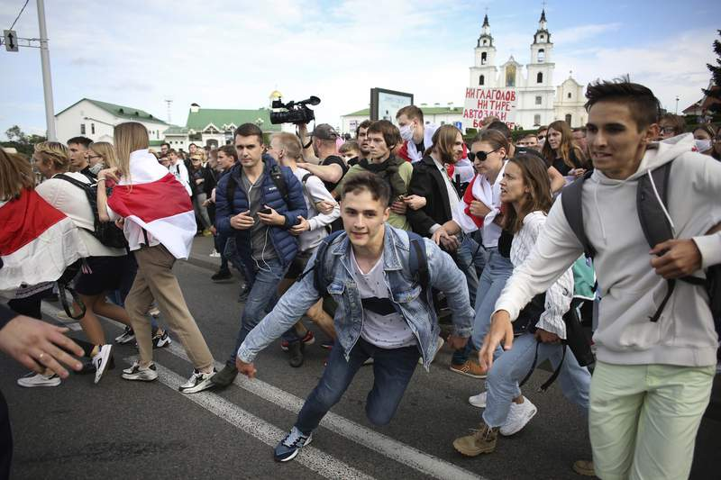 Students run away from police during a protest in Minsk, Belarus, Tuesday, Sept. 1, 2020. Several hundred students on Tuesday gathered in Minsk and marched through the city center, demanding the resignation of the country's authoritarian leader after an election the opposition denounced as rigged. Many have been detained as police moved to break up the crowds. (Tut.By via AP)