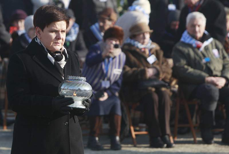 FILE - In this Friday, Jan. 27, 2017 file photo, Polish Prime Minister Beata Szydlo lights a candle at the International Monument to the Victims of Fascism, after a ceremony marking the 72nd anniversary of the liberation of the German Nazi death camp Auschwitz-Birkenau, in Oswiecim, Poland. Three of nine members appointed to an advisory council for the Auschwitz-Birkenau museum in Poland have resigned in protest after the government also named Beata Szydlo, a top right-wing ruling party member, to serve on the body it was announced Friday, April 16, 2021. The culture minister appointed Szydlo recently to a four-year term on the Auschwitz-Birkenau State Museum Council, a body made up of Poles who meet once a year to advise the director but which has little real influence. (AP Photo/Czarek Sokolowski, file)