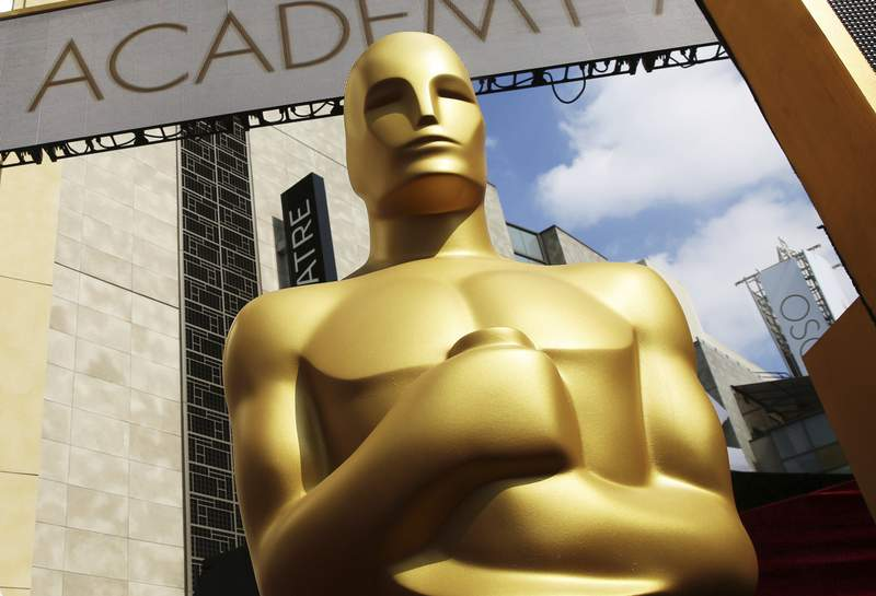 FILE - In this Feb. 21, 2015 file photo, an Oscar statue appears outside the Dolby Theatre for the 87th Academy Awards in Los Angeles. The Oscars are implementing some big changes, including having a set number of best picture nominees and to-be-determined representation and inclusion standards for eligibility. The Academy of Motion Picture Arts and Sciences says Friday that there will be 10 best picture nominees beginning with the 94th Academy Awards in 2022. (Photo by Matt Sayles/Invision/AP, File)