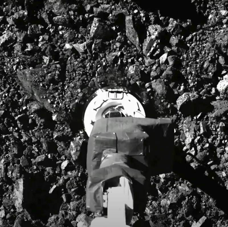 In this image taken from video released by NASA, the Osiris-Rex spacecraft touches the surface of asteroid Bennu on Tuesday, Oct. 20, 2020. (NASA via AP)