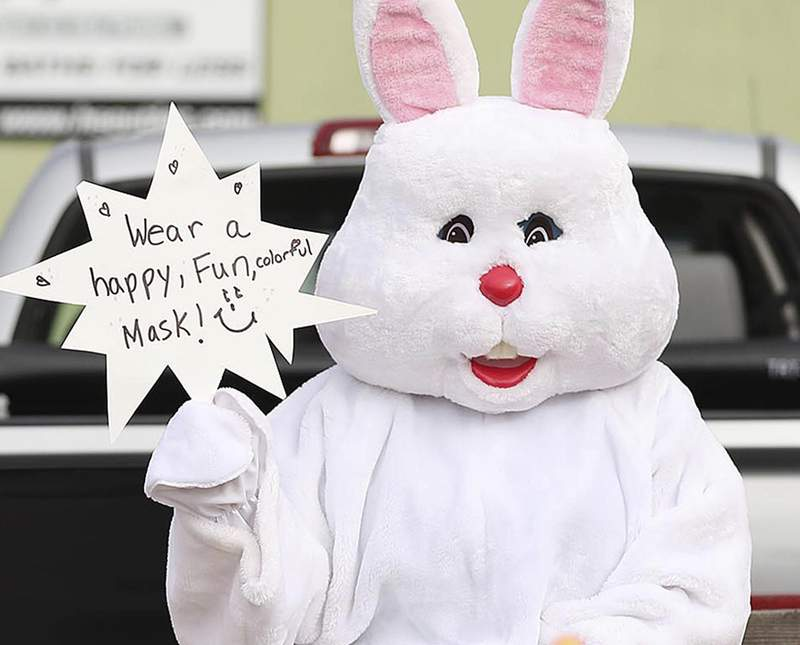 """The Easter Bunny encourages people to wear a mask during an Easter parade in Orlando, Fla.,  on Saturday, April 11, 2020. The parade, conducted with """"social distancing"""" to prevent the spread of coronavirus.   (Stephen M. Dowell/Orlando Sentinel via AP)"""