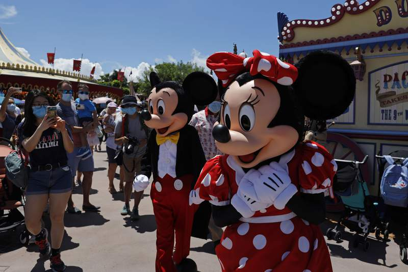 The iconic cartoon characters Minnie and Mickey Mouse walk with the visitors at the Hong Kong Disneyland on Thursday, June 18, 2020. Hong Kong Disneyland on Thursday opened its doors to visitors for the first time in nearly five months, at a reduced capacity and with social distancing measures in place. The theme park closed temporarily at the end of January due to the coronavirus outbreak, and is the second Disney-themed park to re-open worldwide, after Shanghai Disneyland. (AP Photo/Kin Cheung)