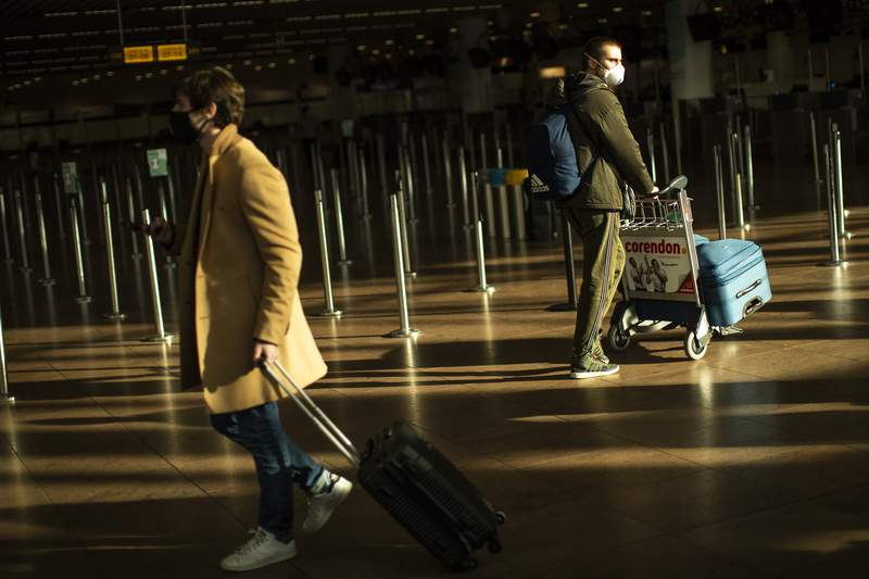 FILE - In this Jan. 22, 2021, file photo, travellers, wearing face masks to prevent the spread of the coronavirus COVID-19, walk along the departure hall of the Zaventem international airport in Brussels. The European Commission proposed Thursday April 29, 2021, issuing Digital Green Certificates to EU residents to facilitate travel across the 27-nation bloc by the summer 2021, as long as they have been vaccinated, tested negative for COVID-19 or recovered from the disease. (AP Photo/Francisco Seco, File)