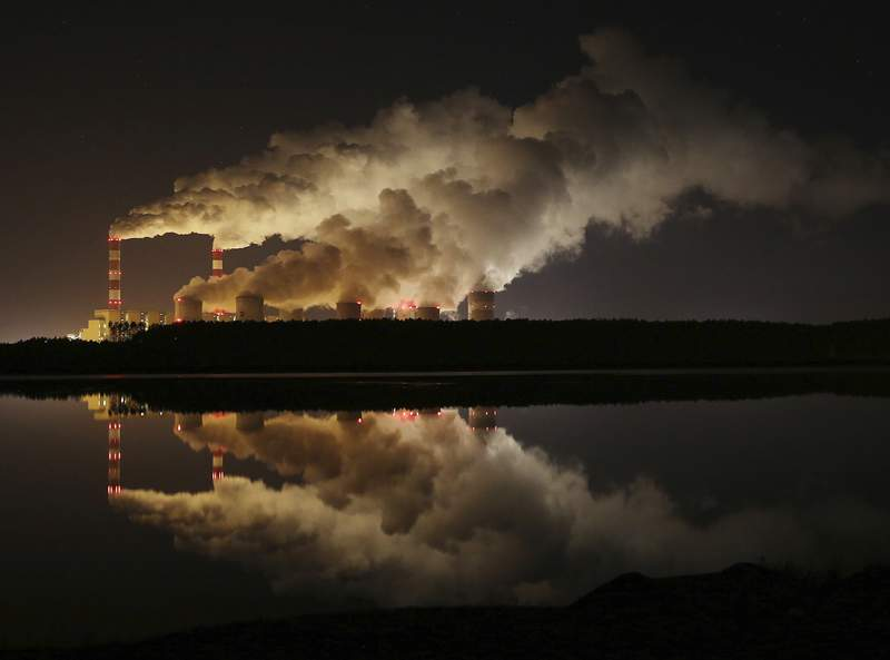 FILE - In this Wednesday, Nov. 28, 2018 file photo, clouds of smoke over Europe's largest lignite power plant in Belchatow, central Poland. Greenhouse gas emissions in the European Union have been reduced by 24% compared to 1990 levels, according to the blocs annual climate report. Still, the EU said Monday, Nov. 30, 2020 it need to intensify efforts to make its target of making Europe the first climate neutral continent by mid-century. (AP Photo/Czarek Sokolowski, file)