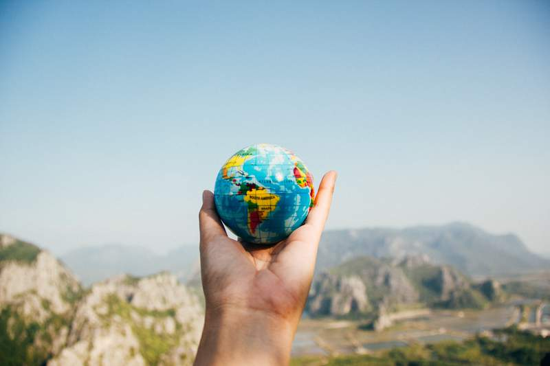 A person holds up a tiny globe.