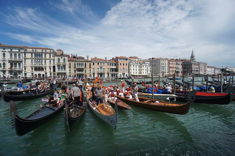 FILE - In this Sunday, June 21, 2020 file photo, gondolas are lined up during the Vogada della Rinascita (Rowing of Rebirth) regatta, along Venice canals, Italy. European Union envoys are close to finalizing a list of countries whose citizens will be allowed back into Europe once it begins lifting coronavirus-linked restrictions. The United States appears almost certain not to make the list, as new infections surge and given that President Donald Trump has imposed a ban on European travelers. (Anteo Marinoni/LaPresse via AP, File)