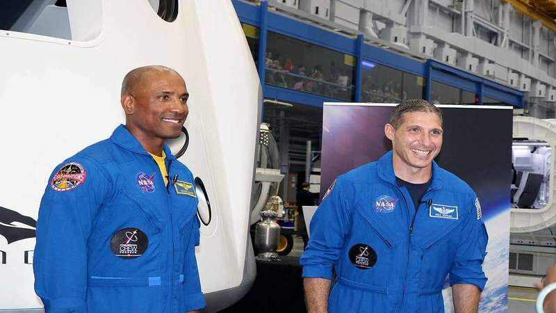 NASA astronauts Victor Glover, left, and Michael Hopkins, right, in front of a mock up of the SpaceX Crew Dragon on Aug. 3, 2018 at NASA's Johnson Space Center. (Photo: Emilee Speck/WKMG)