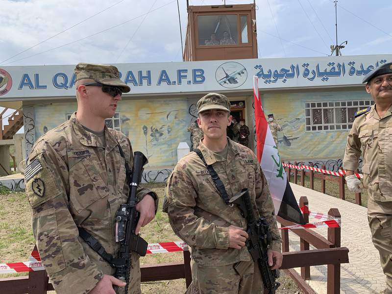 U.S. soldiers stand guard during the hand over ceremony of Qayyarah Airfield, Iraqi Security Forces, in the south of Mosul, Iraq  early Friday, March 27, 2020. Iraq's military on Thursday said at least two rockets hit inside Baghdad's heavily fortified Green Zone, the seat of Iraq's government and home to the American Embassy, in the first attack following a brief lull in violence from earlier this month. (AP Photo/Ali Abdul Hassan)