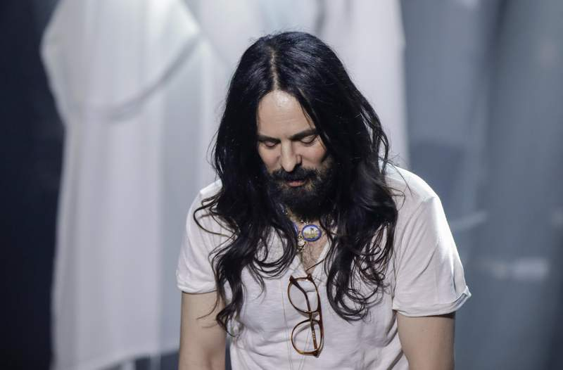 FILE - In this Wednesday, Feb. 19, 2020 file photo, Alessandro Michele acknowledges the applause of the audience at the end of Gucci's Fall/Winter 2020/2021 collection, presented in Milan, Italy. Gucci creative director Alessandro Michele is celebrating the fashion houses 100-year anniversary, giving historic sweep to a collection unveiled virtually Thursday that embraced its equestrian heritage, borrowed references from the Tom Ford-era and outright stole from a sister brand Balenciaga. (AP Photo/Luca Bruno, File)