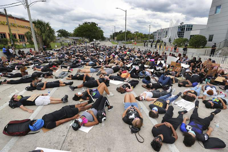 Protestors lie down on South Street in front of the Orlando Police Department in Orlando, Fla., Friday, June 5, 2020. The protests continue in Orlando on Friday over the death of George Floyd when he was in police custody in Minneapolis on May 25. (Joe Burbank/Orlando Sentinel via AP)