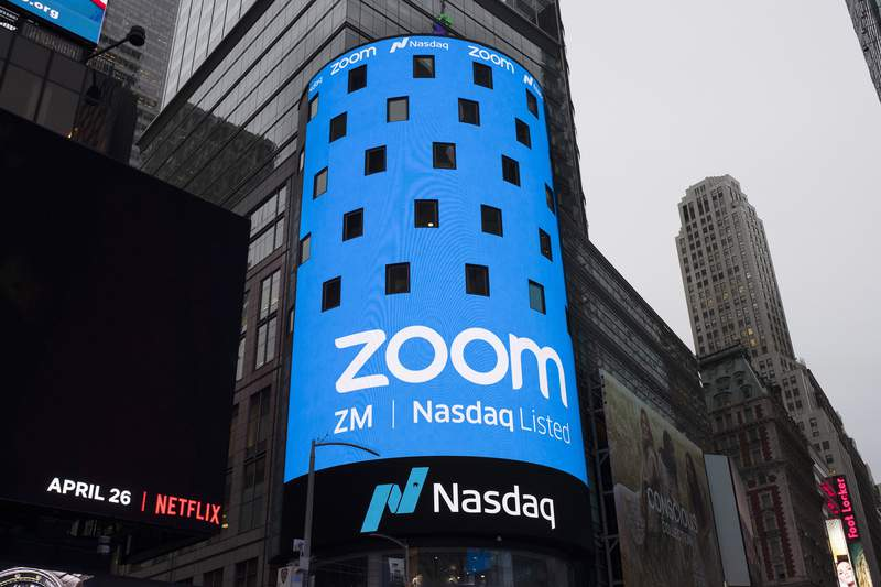 FILE - This April 18, 2019, file photo shows a sign for Zoom Video Communications ahead of the company's Nasdaq IPO in New York. Zooms astronomical growth is tapering off along with the pandemic. That's raising questions about whether the videoconferencing services immense popularity will fade as more people return to classrooms, offices and other places off limits for the past year. The deceleration emerged in an otherwise impressive quarterly earnings report released Monday, March 1, 2021. (AP Photo/Mark Lennihan, File)