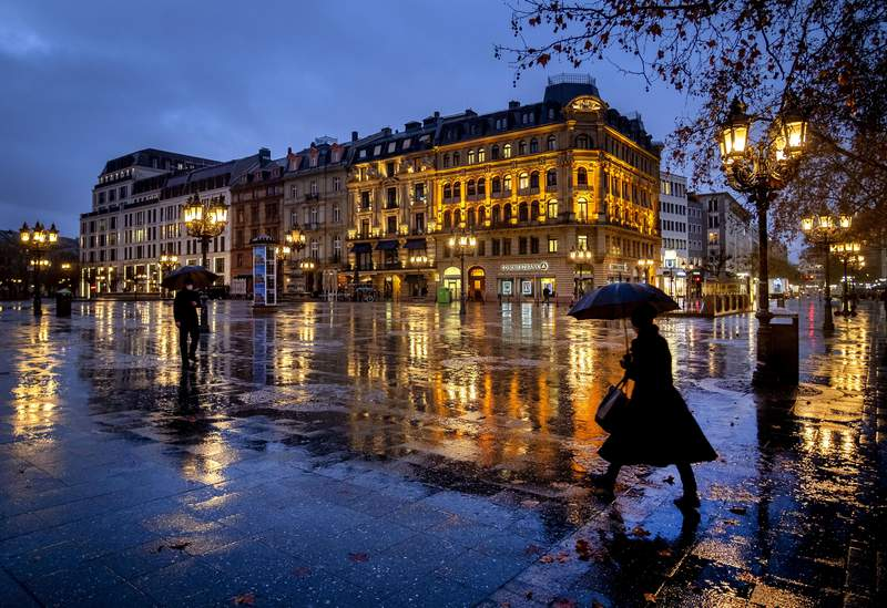 People under umbrellas on the square in front of the Old Opera in Frankfurt, Germany, on a rainy Friday morning, Jan. 22, 2021. (AP Photo/Michael Probst)