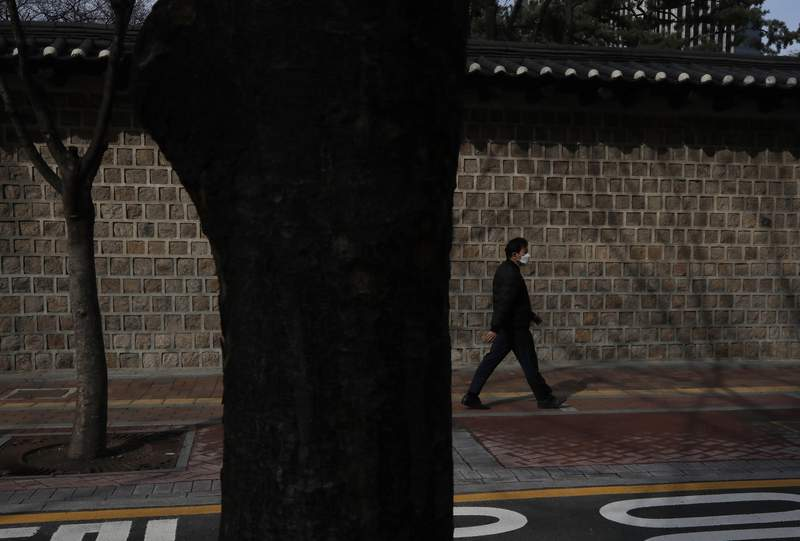 A man wearing a face mask walks along a wall outside the Deoksu palace in downtown Seoul, South Korea, Friday, March 13, 2020. For most people, the new coronavirus causes only mild or moderate symptoms, such as fever and cough. For some, especially older adults and people with existing health problems, it can cause more severe illness, including pneumonia. (AP Photo/Lee Jin-man)