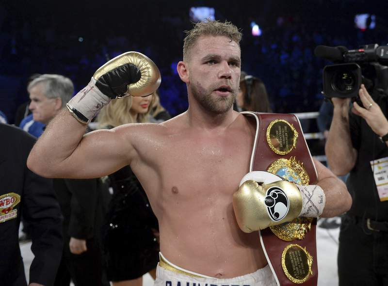 FILE - In this Dec. 16, 2017, file photo, Billy Joe Saunders, of Britain, celebrates his win over David Lemieux, of Canada, to retain the WBO middleweight boxing title in Laval, Quebec. Saunders had his boxing license suspended Monday, March 30, 2020, after publishing a social media video in which he appeared to condone domestic violence amid the coronavirus outbreak. He has apologized for his remarks, saying: It was a silly mistake but I didn't mean to cause any harm to anyone and I certainly wouldn't promote domestic violence.(Ryan Remiorz/The Canadian Press via AP)